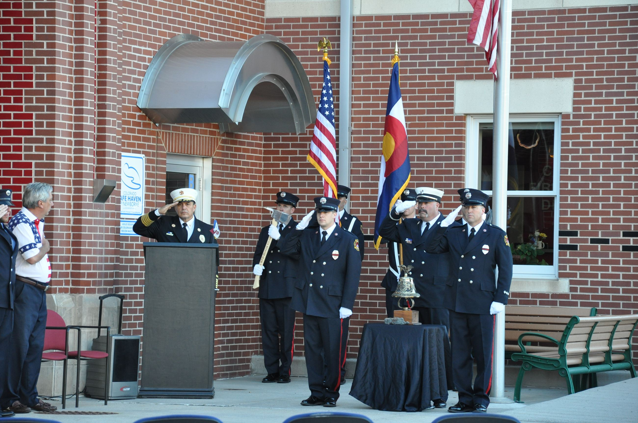 Honor guard and other fire department personnel saluting
