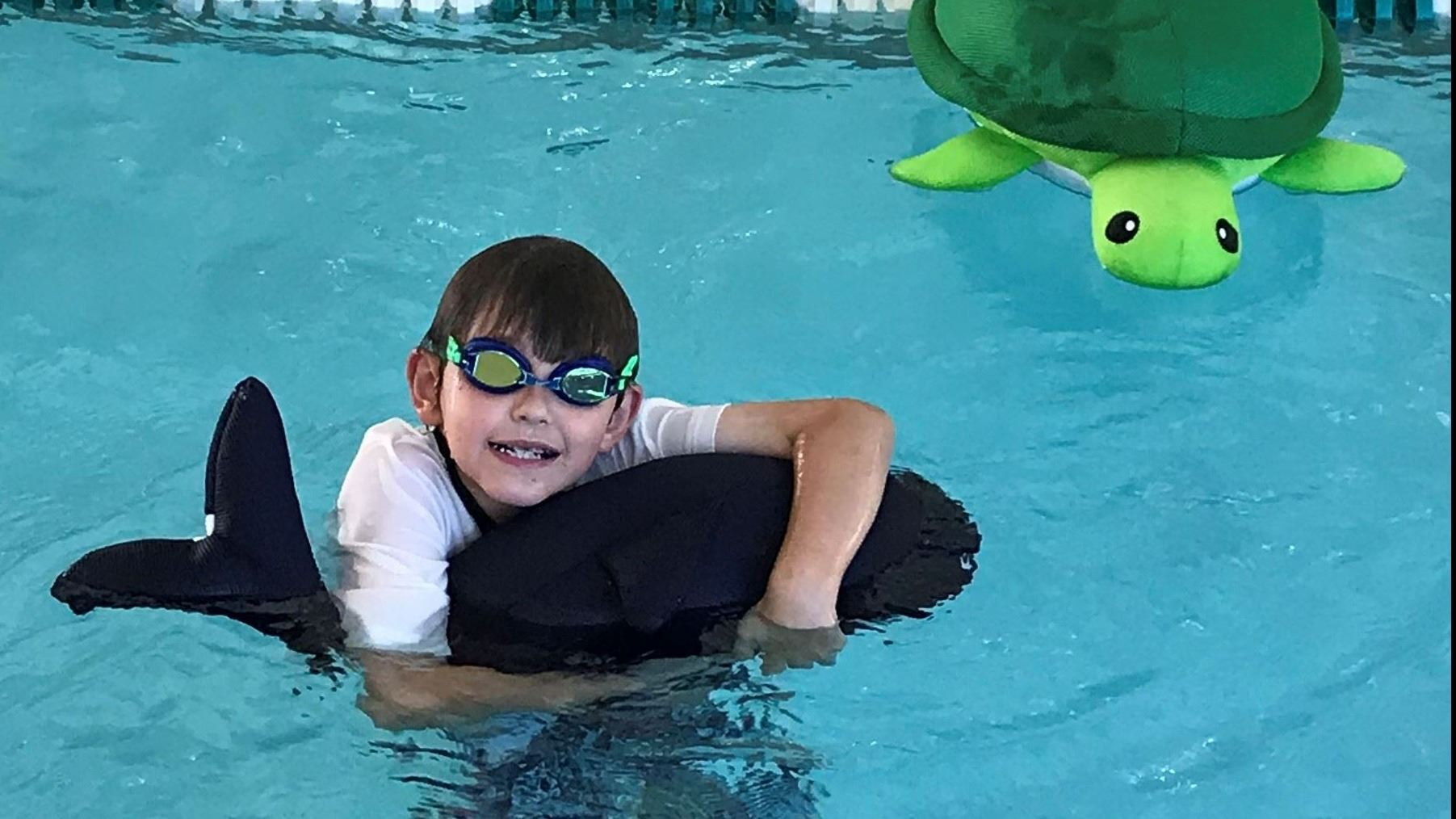 Adaptive Swimming student with floaty animals in the pool