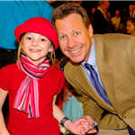 a young girl dressed in modern french styled hat, scarf and dress smiling with her dad