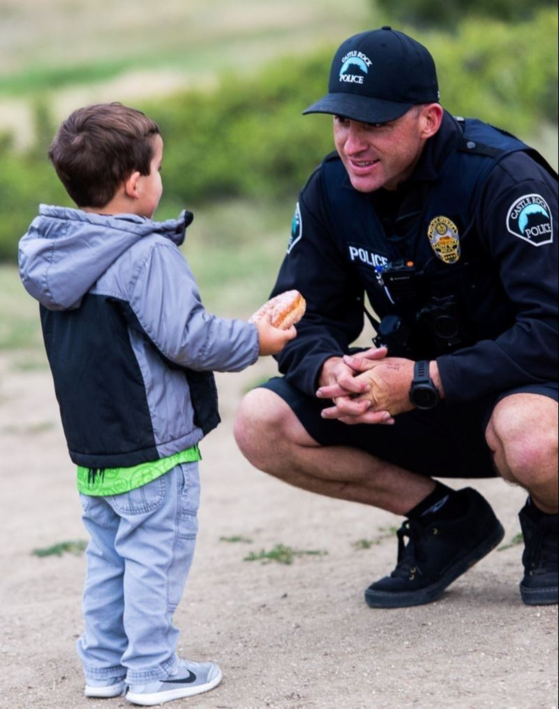 Officer with a child at a Donuts and Jumps event